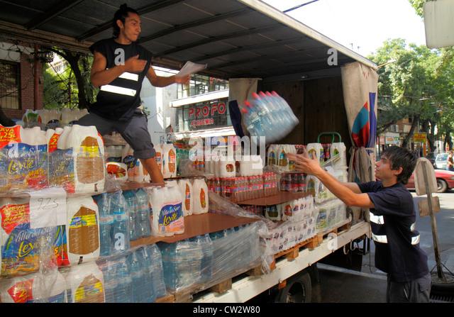 Argentina Mendoza Avenida San Juan delivery truck retail distribution bottled water soft drink physical labor unload - Stock Image