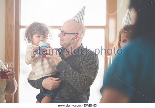 Mature man feeding toddler granddaughter a drink - Stock Image