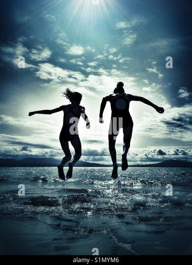 Two young girls having fun jumping over waves at Newborough beach on Anglesey. - Stock Image