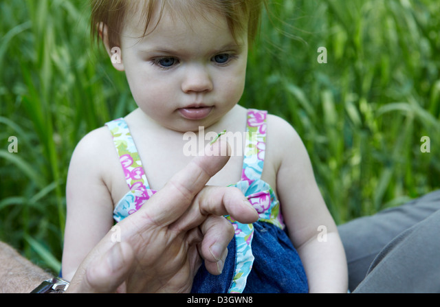 1 year old girl looks at green caterpillar - Stock Image