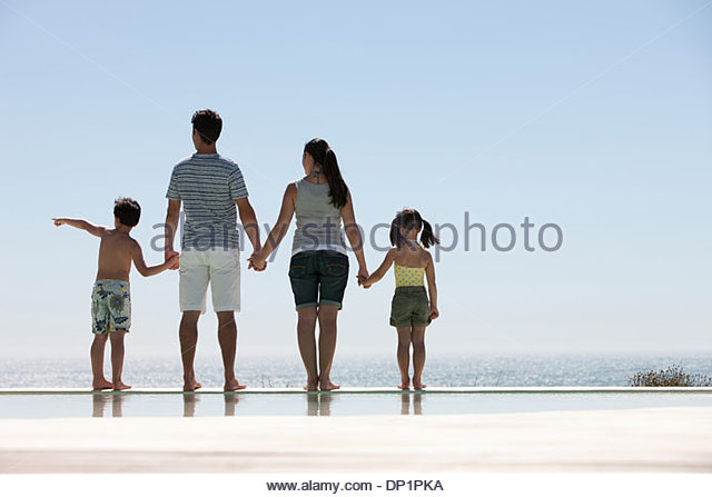 Family standing at edge of infinity pool with ocean in background - Stock Image