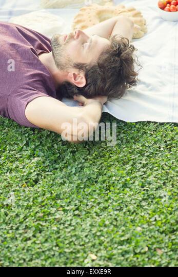 Man napping after picnic - Stock Image