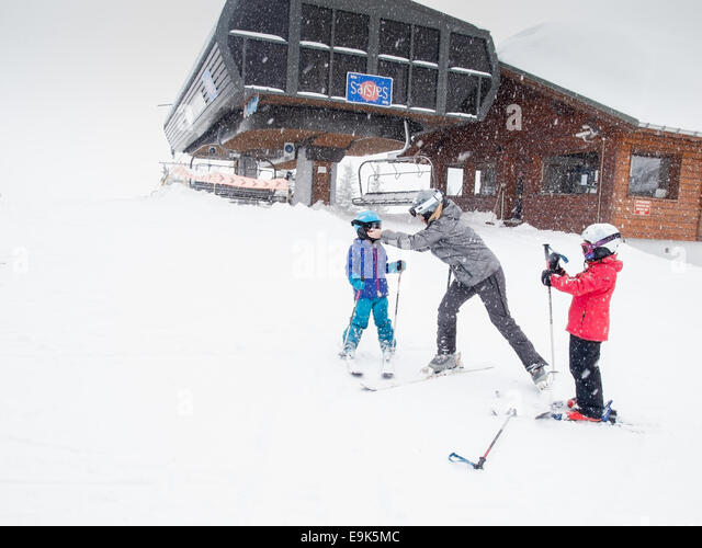 young family preparing to go skiing in front of a ski lift in heavy falling snow - Stock Image