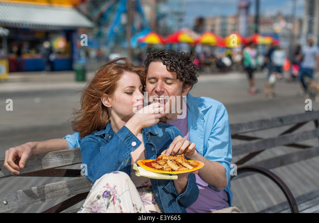 Romantic couple eating chips at amusement park - Stock-Bilder