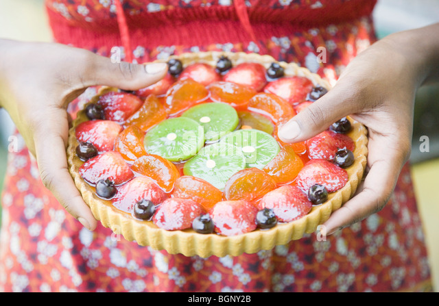 Mid section view of a woman holding a fruit pie - Stock-Bilder
