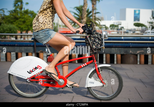 woman rides a bicing community hire bicycle in barcelona - Stock Image