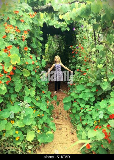A girl standing in a tunnel of vines and flowers. - Stock Image
