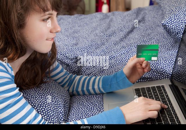 Girl lying on bed with laptop internet shopping - Stock-Bilder