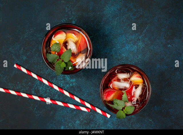 Peach ice tea in glass on  concrete blue background. view from above - Stock Image