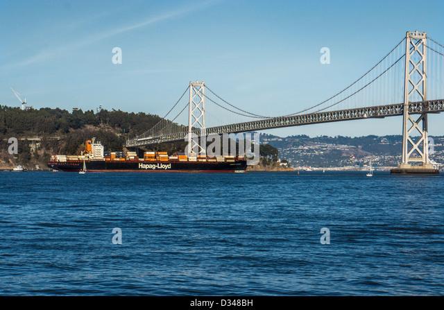 Container cargo ship passing under the Bay Bridge in San Francisco California - Stock Image