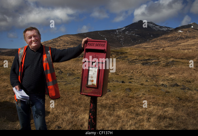 Alastair, Isle Of Mull Postie (postman), western Scotland UK , emptying red post box - Stock Image