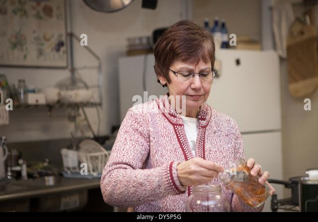 Health foods store owner putting herbs in jars - Stock Image