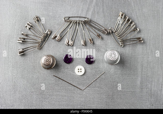 Smiling face of a girl built of sewing items on grey background - Stock Image