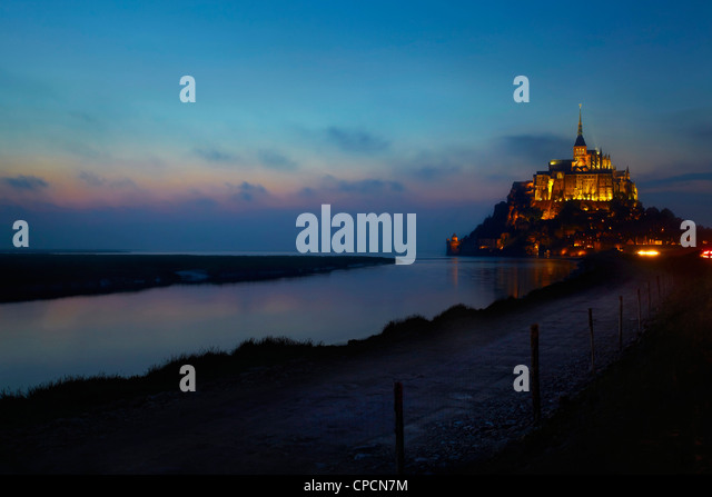 Castle on lake lit up at night - Stock Image