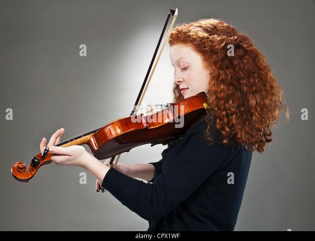 Portrait of mixed race teenage girl playing violin - Stock Image