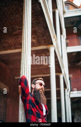 Man with beard leaning against a pillar - Stock-Bilder