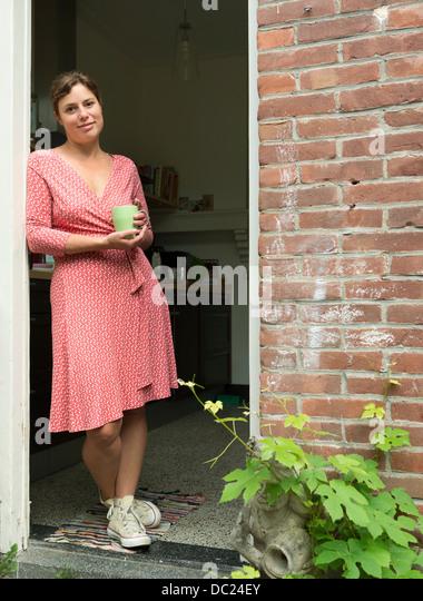 Woman standing in doorway holding mug - Stock Image
