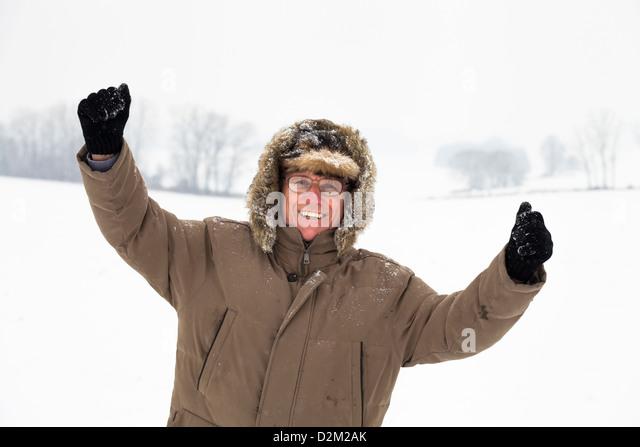 Happy ecstatic senior man enjoying snow and winter outdoors. - Stock Image