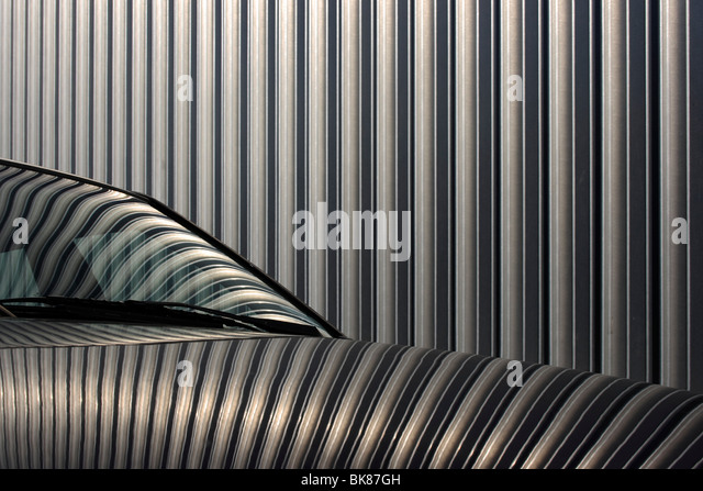 Reflection of the facade of an exhibition hall in the paint of a car - Stock Image