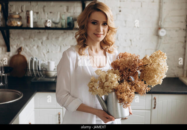 Middle Eastern holding kettle of flowers in domestic kitchen - Stock-Bilder