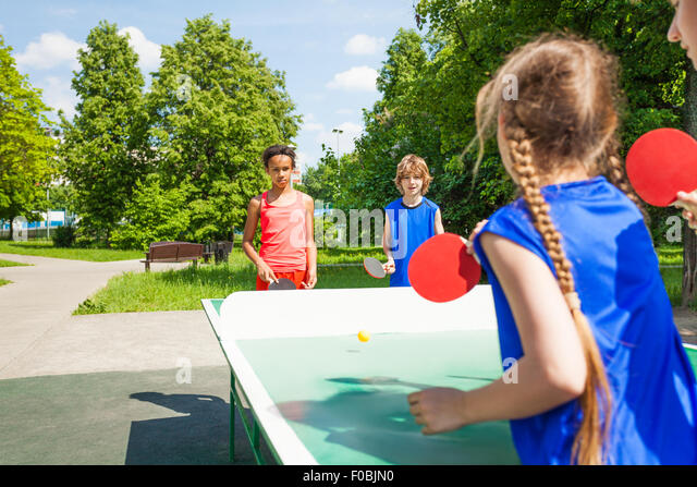 Four international friends play table tennis - Stock Image