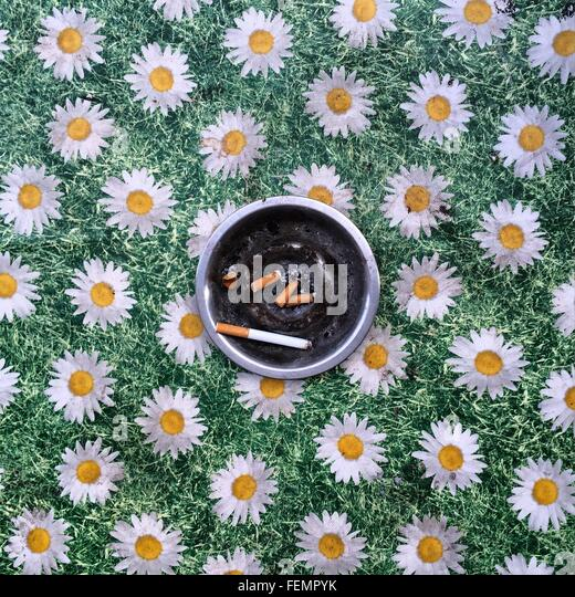 Ashtray On Floral Pattern Tablecloth - Stock Image