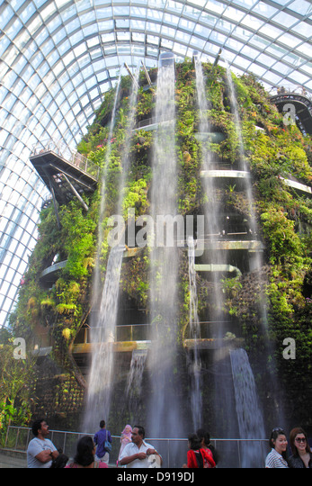 Singapore Gardens by the Bay park Cloud Forest mountain greenhouse waterfall Asian family man woman - Stock Image