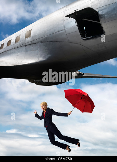 humorous image of woman holding umbrella falling from open hatch of airplane in flight - Stock Image