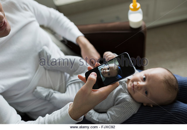 Father photographing baby son on lap camera phone - Stock Image