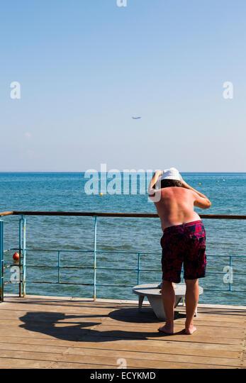 Plane spotter on the peir at Finikoudas, Larnaca, Cyprus. - Stock Image