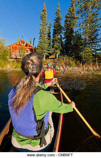 Canoeists on Willow Lake paddle back to lakeside Cabin and Willow Lake B&B, Copper River Basin, Southcentral - Stock Image