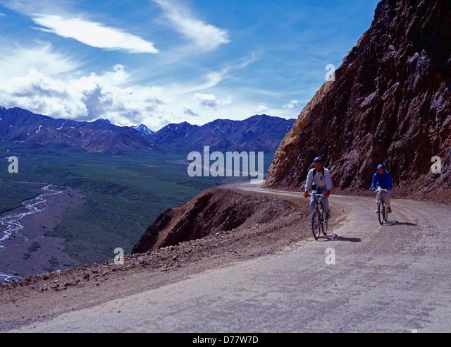 Couple mountain biking park road over Polychrome Pass Denali National Park Alaska. - Stock Image