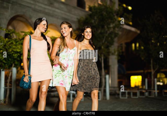 Women walking on city street at night - Stock Image
