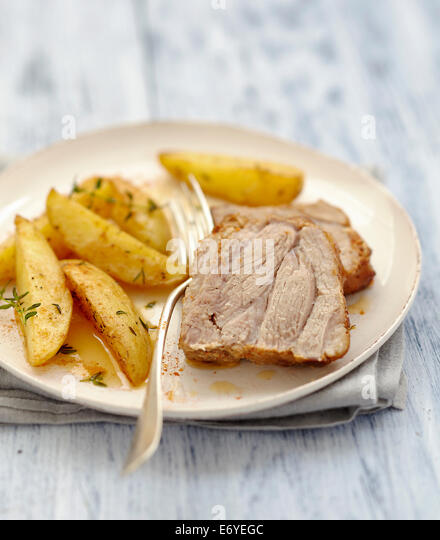 Roast pork marinated in spices,fried potatoes with thyme - Stock Image