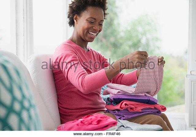 mid adult woman folding clean laundry - Stock-Bilder