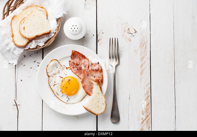 Fried egg with grilled sausage for breakfast - Stock Image