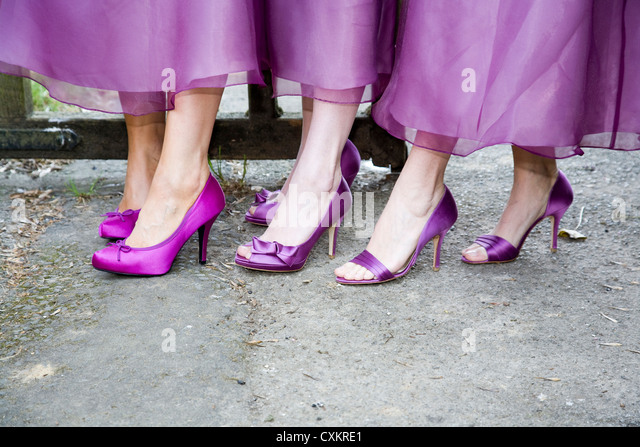 Bridesmaid's feet and ankles with purple high heeled shoes, showing hems of dresses. - Stock-Bilder