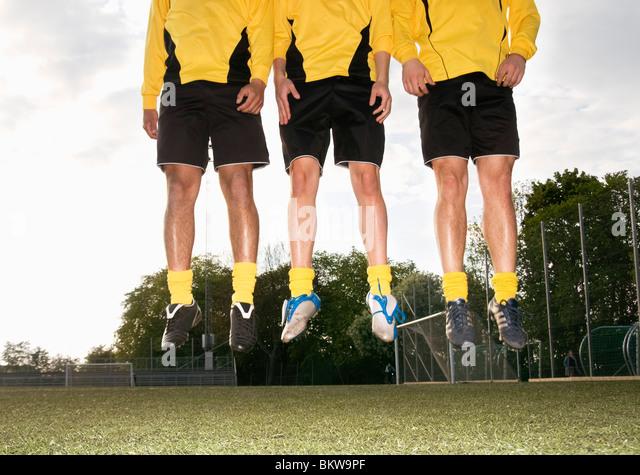 Three football guys jumping - Stock-Bilder