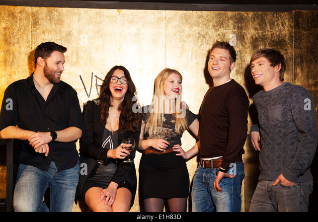 Group of friends having a laugh in nightclub - Stock Image