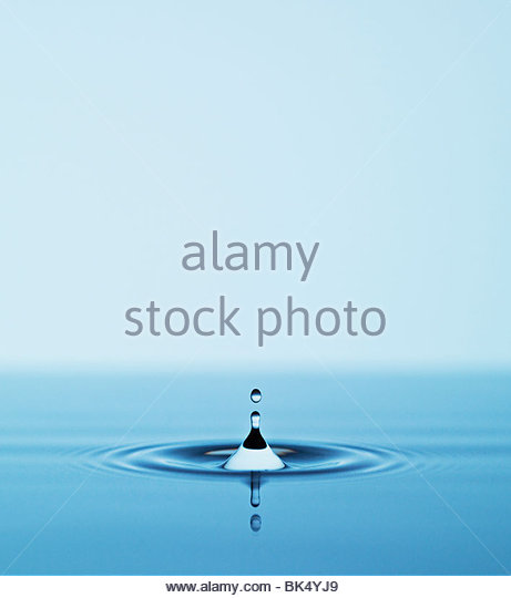 Close up of droplet falling in pool of water - Stock Image
