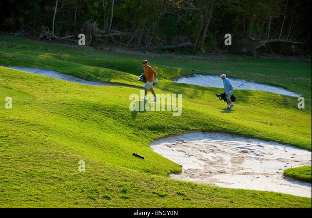 Bermuda golf course st george parish sand trap two men playing golf - Stock Image