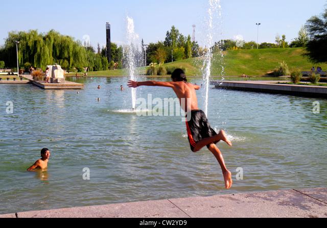 Mendoza Argentina Parque General San Martin public park artificial lake water Hispanic boy teen swimming swim cool - Stock Image