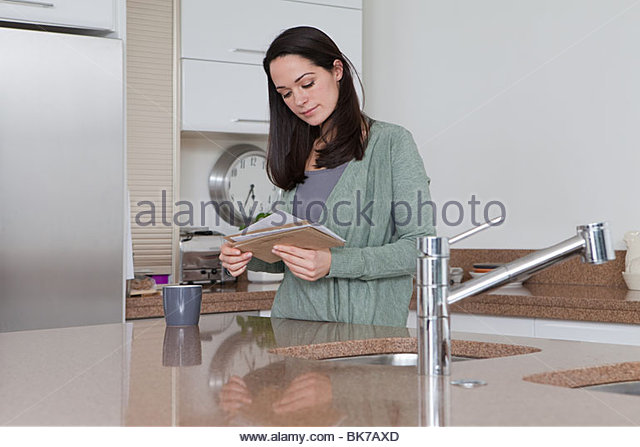 Young woman in kitchen looking at mail - Stock Image