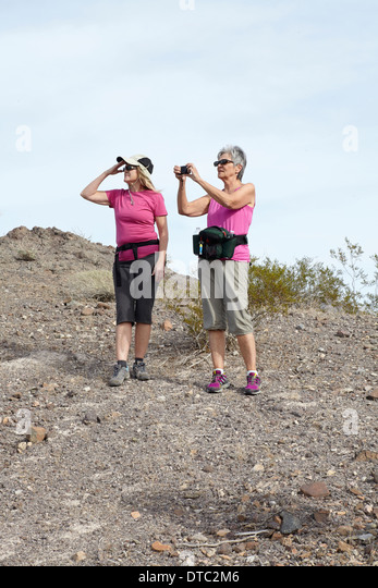 Two senior female hikers looking and photographing view - Stock Image
