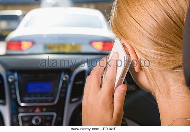Female Driver Talking On Phone Whilst Driving - Stock Image