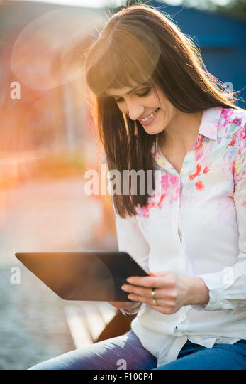 Young beautiful woman sitting on bench in street and browsing internet on tablet - Stock Image