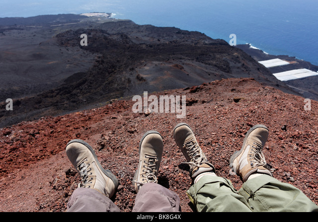 Feet with walking boots, hikers taking a break on the Teneguía Volcano, La Palma, Canary Islands, Spain, Europe - Stock Image