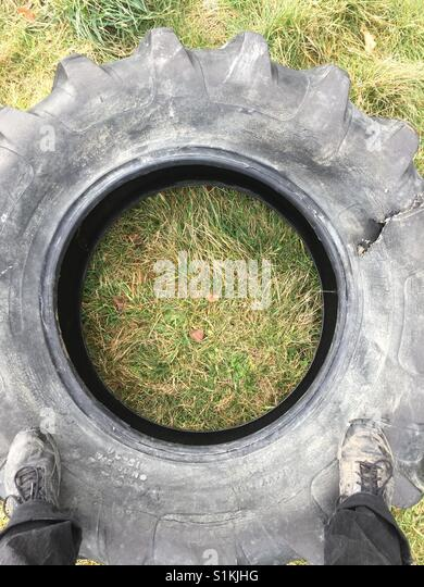 Feet on a tyre - Stock Image