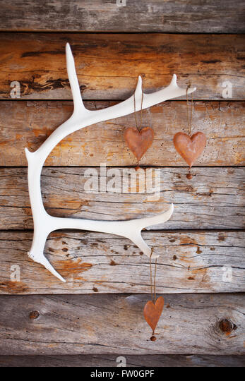 Rustic hearts hanging from white reindeer antler - Stock Image