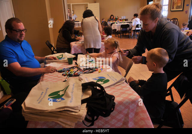 Joshua Potter, 92nd Civil Engineer Squadron air program manager, instructs children as they color on recyclable - Stock Image